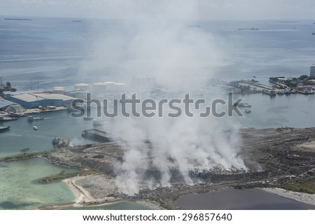 Burning garbage heap of smoke from a burning pile of garbage on island. - stock photo