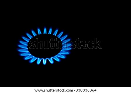 burning gas stove hob blue flames close up in the dark on a black background - stock photo