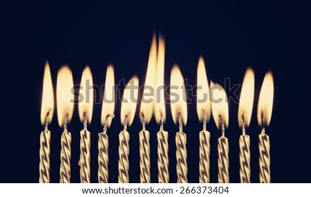 Burning golden candles on blue background - stock photo