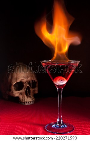 Burning halloween cocktail with skull and glass eye - stock photo