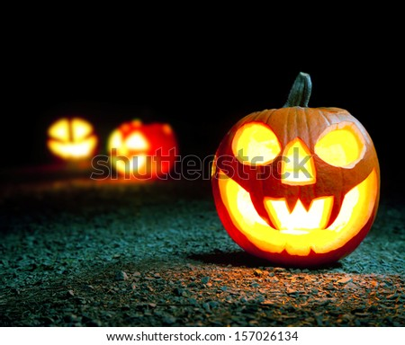 Burning halloween pumpkin in forest - stock photo