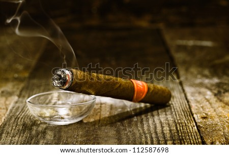Burning handmade luxury Cuban cigar resting on an ashtray on an old wooden countertop in a nightclub or bar with copyspace - stock photo