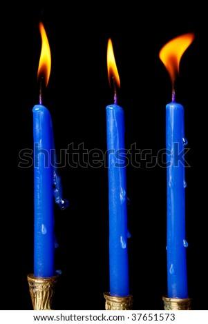 burning hanukkah candles in a menorah on black background - stock photo