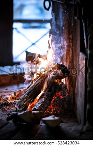 Burning home fireplace with logs in a wooden house in the woods in winter weather Christmas