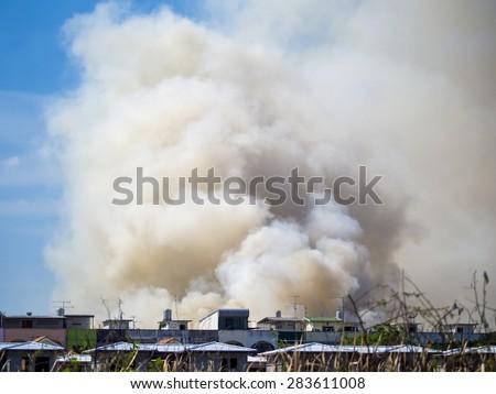 Burning house causes a big pile of smoke, black smoke rising up to blue sky background. - stock photo