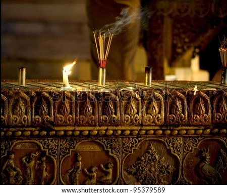 burning incense and candles in a temple / church