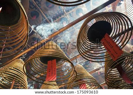 Burning incense coils inside Man Mo Temple, Hong Kong - stock photo