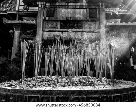 Burning Incense sticks in joss-stick pot with light ray - stock photo