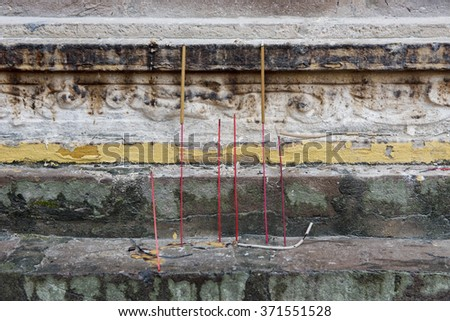 Burning incense sticks on the steps of an ancient burial tower of the Tran Quoc Pagoda, Hanoi, Vietnam.  The towers contain the ashes of the original monks of the Pagoda. - stock photo