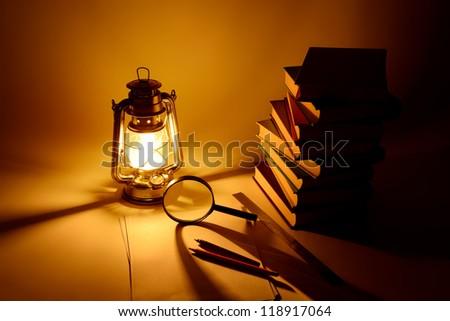 Burning kerosene lamp and books, concept magic of light - stock photo