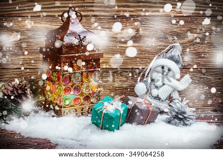 burning lantern and gifts in the snow on a wooden table. focus on gifts - stock photo