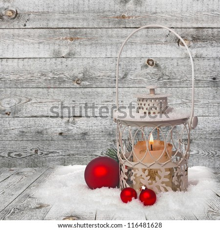 Burning lantern in the snow on wooden background - stock photo