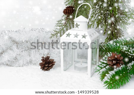 Burning lantern, spruce branches with cones and Christmas tinsel, horizontal
