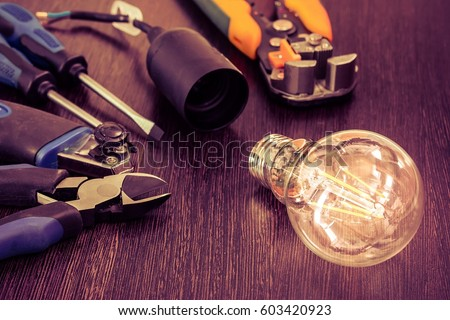 burning light bulb and socket and other electrician tools are on the table