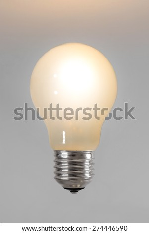 Burning light bulb on a gray background