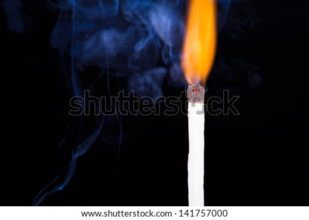 Burning match flame and smoke on dark background.