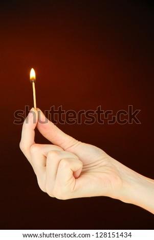 Burning match in female hand, on dark brown background - stock photo