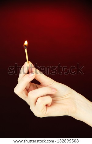 Burning match in female hand, on dark red background - stock photo