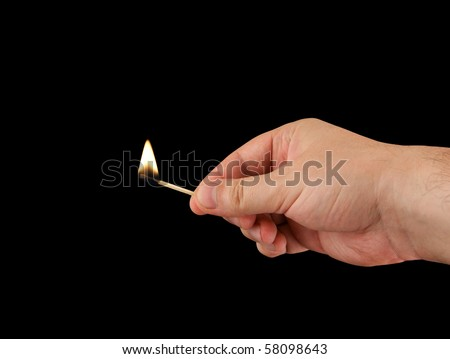 Burning match in hand on a black background