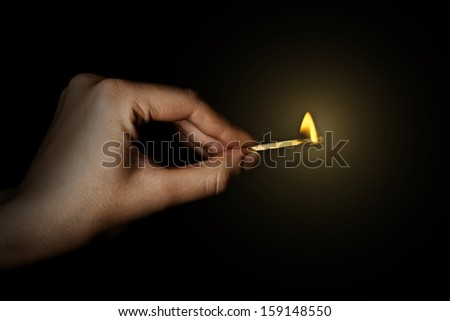 Burning match in hand on black background