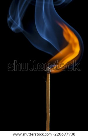 Burning match on a black background - stock photo