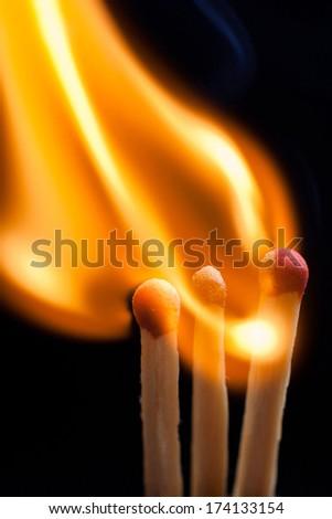 burning match on black background - stock photo