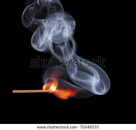 burning match with the smoke. Isolated on black background