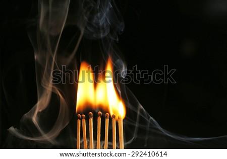 Burning matches in smoke on black background - stock photo