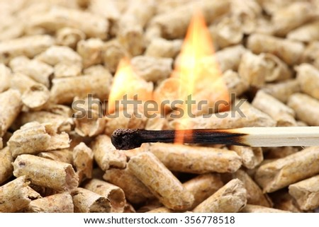 burning matchstick in front of wood pellets - stock photo