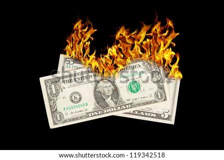 Burning money, dollar bills on fire, isolated on black - stock photo