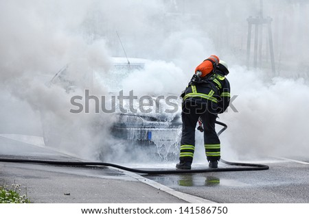 Burning motor vehicle been put out by fireman in protective clothing - stock photo