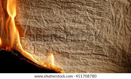 Burning old paper on black backgrounb. - stock photo