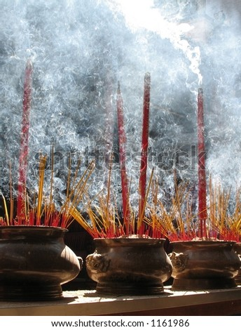 Burning prayer sticks fill the room with swirling smoke.  Thien Hau Pagoda, Cholon (China Town), Ho Chi Minh, Vietnam. - stock photo