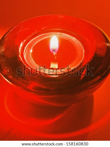 burning red tea candle in a glass bowl - stock photo