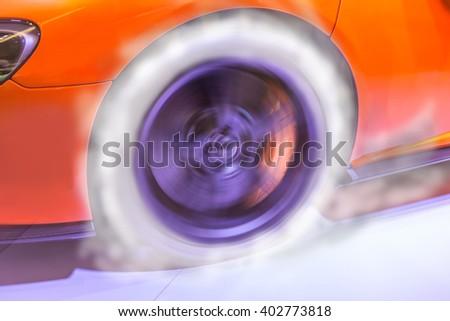 Burning rubber of orange car. - stock photo