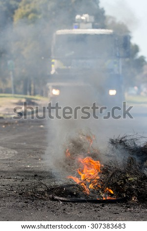 Burning rubber tyres in the streets in South Africa with police riot vehicle in the background