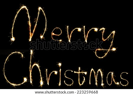 burning sparkler stick and writing Merry Chistmas sparkling words on black background - stock photo