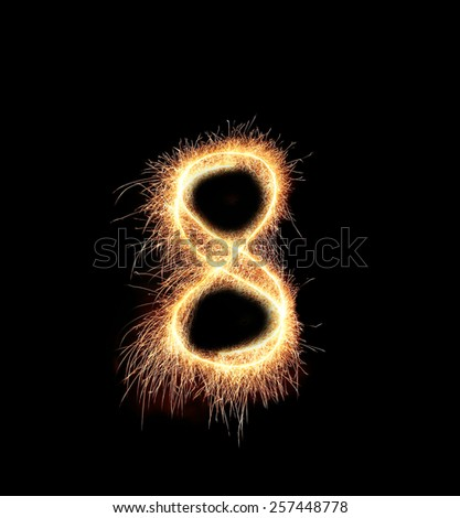 burning sparkler stick and writing sparkling text . number eight isolated on black background - stock photo