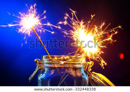 burning sparklers in a jar on wooden table on blue background - stock photo