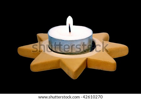 Burning tea light (Candle) in the Christmas-star in front of black background. - stock photo