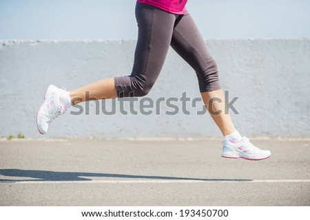 Burning the miles away.  Side view close-up image of woman running outdoors  - stock photo