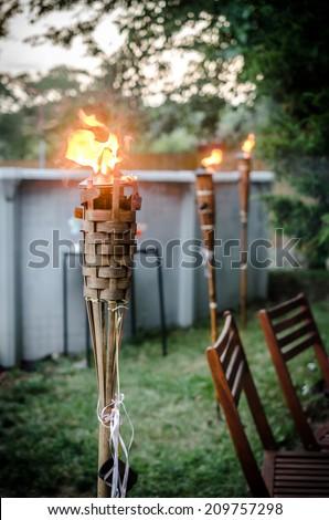 Burning tiki torch in the backyard - stock photo