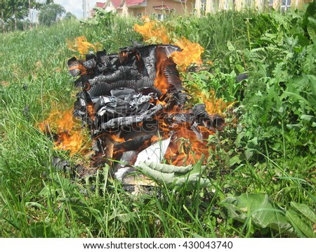 burning trash , on a green lawn , paper box with paper waste , bonfire in the green grass