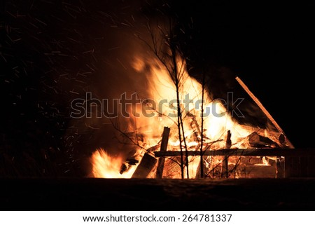 Burning wood house. Ruins. Dark night. Light sparkles flying around the trees