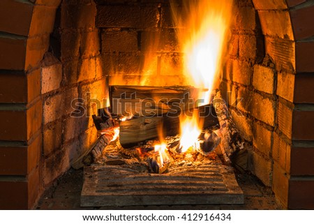 burning wood in brick fireplace in country cottage - stock photo