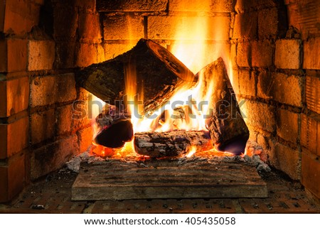 burning wood in fire-box of fireplace in country cottage - stock photo