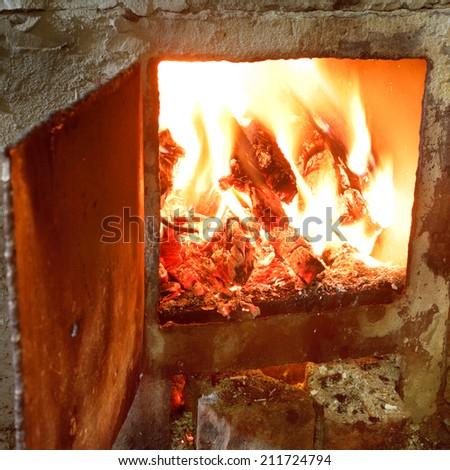 burning wood in furnace with open door close up - stock photo