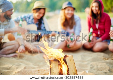 Burning wood on background of restful friends - stock photo