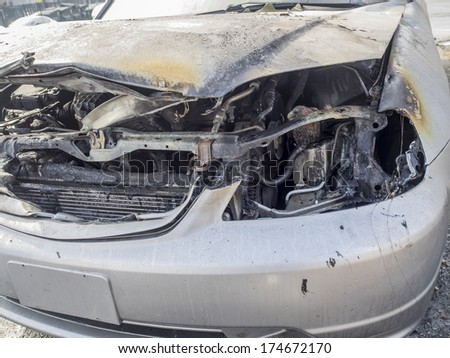 Burnt car with open hood - stock photo