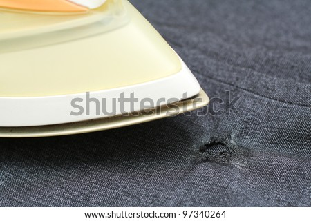 Burnt hole in garment during ironing - stock photo